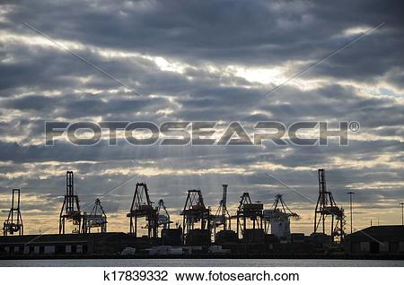 Stock Photo of Heavy industry cranes in logistic bay area in the.