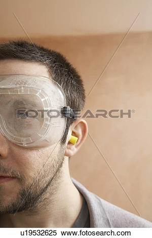 Stock Image of Man wearing protective eye goggles and earplugs.