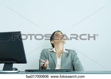 Stock Images of Businesswoman holding yinyang balls, sitting at.