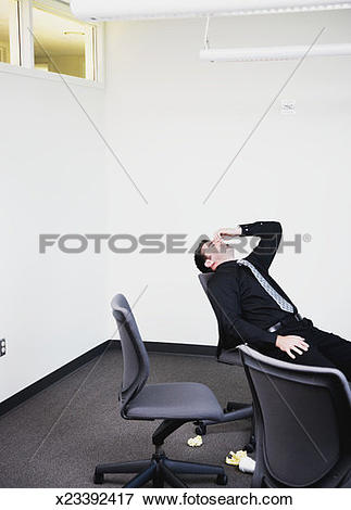 Picture of Businessman leaning back in chair, hand on head, eyes.