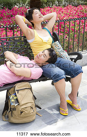 Picture of Man resting head on woman's lap on park bench, eyes.