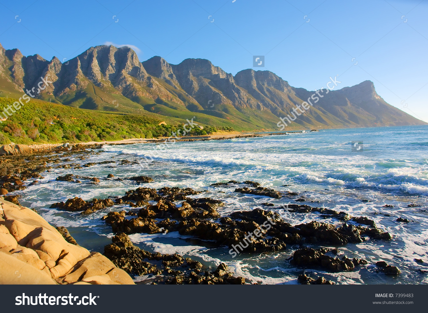 Beach With Rocks And Misty Mountains In Sunset Light. Shot In.
