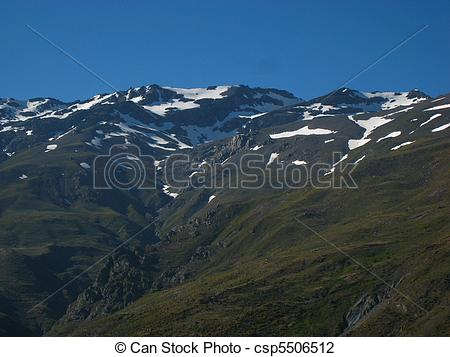Stock Photo of Snowy mountains far away with blue sky.