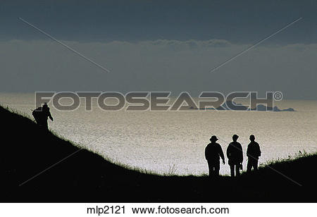 Stock Photography of Silhouetted hikers see the Farallon Islands.
