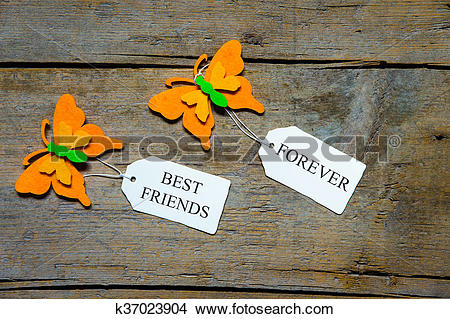 Stock Photo of felty butterflies and white signs on wooden table.