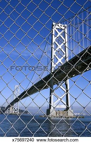 Stock Photography of Oakland Bay Bridge through chain link fence.