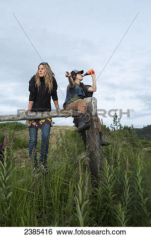Stock Images of Two women sitting on a wooden fence above Halibut.