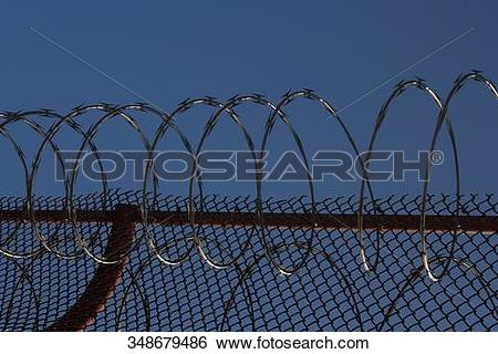 Stock Images of Razor wire and chainlink fence on the bridge.