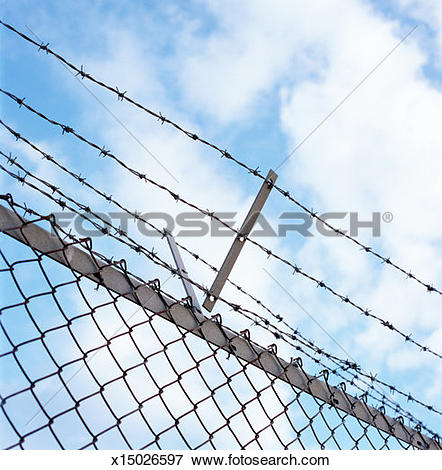Picture of Barbed wire running along top of chain link fence, low.