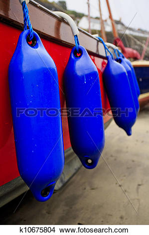 Stock Photo of Brightly covered boat with fenders k10675804.