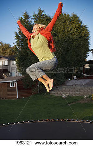 Stock Photography of woman jumps on a trampoline with arms raised.