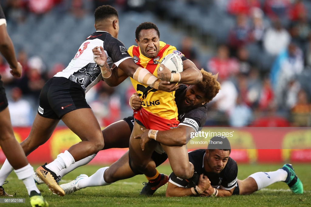 Justin Olam of PNG is tackled by the Fijian defence during the 2018.