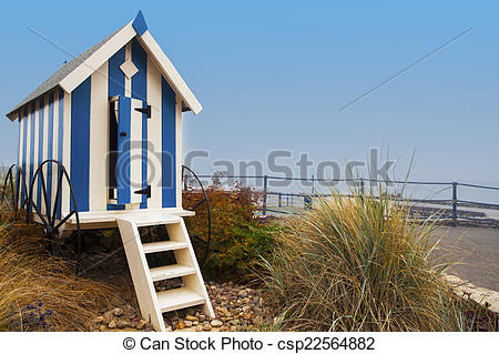 Pictures of Striped blue beach hut on Filey promenade with foliage.