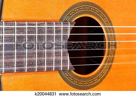 Stock Photography of fingerboard and sound hole of acoustic guitar.