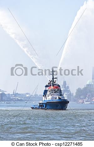 Pictures of Blue fire boat on harbor spraying bright streams of.