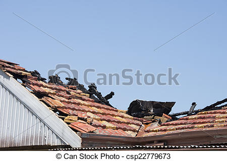 Picture of Chared timber beams on fire damaged roof of house.
