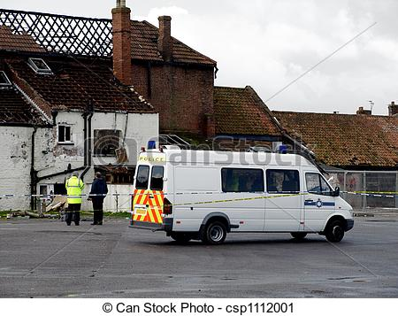 Stock Photography of Crime Scene Fire Damaged House with police.