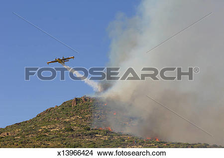 Stock Photo of Fire fighting plane dropping water x13966424.