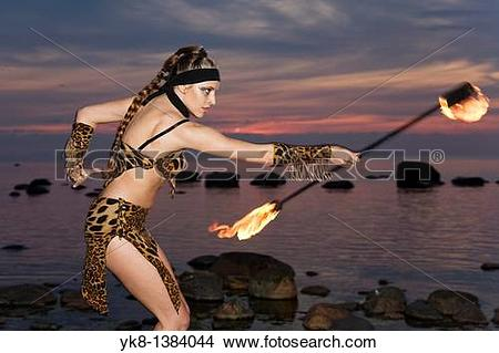 Stock Photo of Semi Nude Woman Fire Dancer in Costume Juggling.