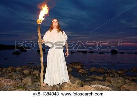 Pictures of Man Fire Dancer in White Costume Holding Torch by.