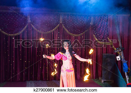 Stock Photography of Fire Dancer Twirling Flaming Batons on Stage.