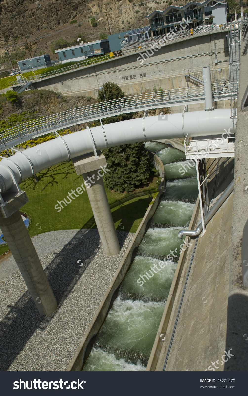 A Fish Ladder Runs Under A Spillway Pipe At A Hydroelectric Dam.