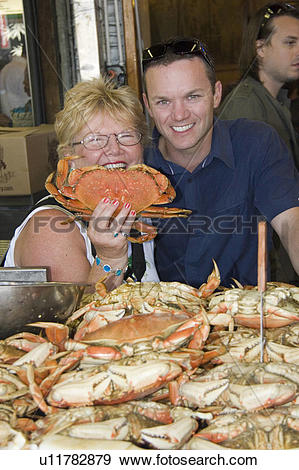 Stock Photograph of Woman and man holding a Dungeness Crab at.