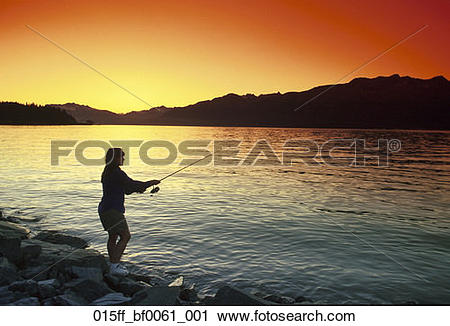 Stock Photography of Woman fishing sunset Prince William Sound.