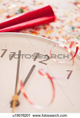 Stock Photography of Confetti and ribbons on clock showing five.