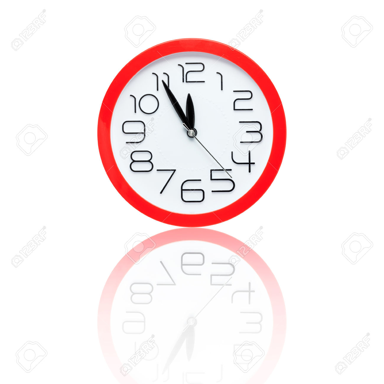 Red Alarm Clock Showing Five Minutes To Midnight With Reflection.