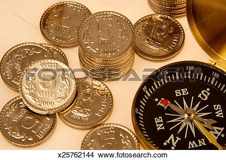 Stock Photo of Stack of five rupees coins beside a compass.