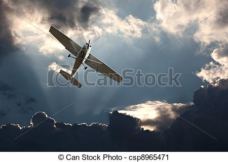 Stock Photography of Small fixed wing plane against a stormy sky.