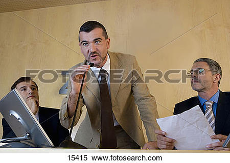 Stock Image of Businessman speaking into microphone, flanked by.