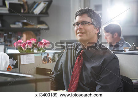 Stock Photograph of Man sitting at desk in office (lens flare.