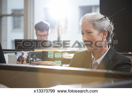 Stock Photograph of Woman working at desk in office, man in.
