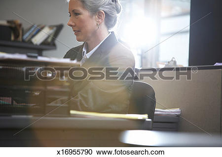 Stock Photography of Woman working at desk in office (lens flare.
