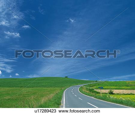 Stock Photo of a Road, Surrounded By a Green Flat Land Under a.