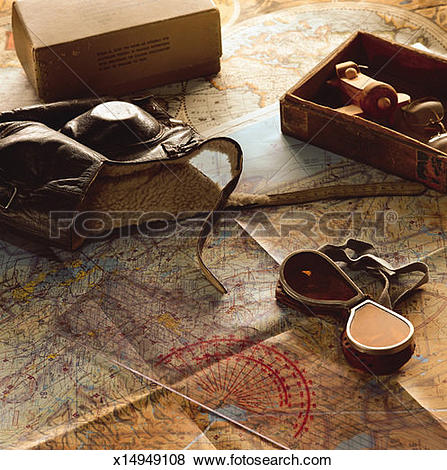 Pictures of flight gear and maps lay on a flat surface with filled.