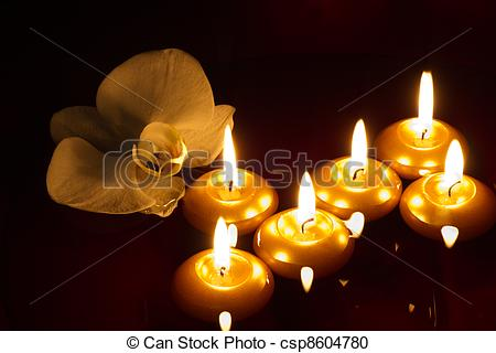 Stock Photography of Floating candles and orchid in dark.