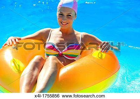 Stock Images of Young woman has fun with an floating tire in.