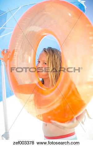 Pictures of Girl on beach inflating an orange floating tyre.