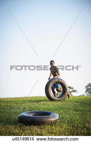 Stock Photo of A teenage boy running across the grass rolling a.