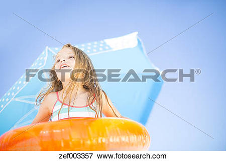 Picture of Smiling girl on beach holding an orange floating tyre.