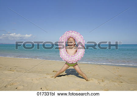 Stock Photo of little girl with floating tyre on beach 017331bl.