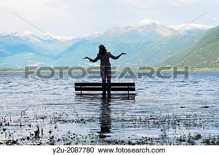 Stock Photography of Woman standing on a bench in a flooding.