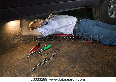 Stock Photograph of A mechanic lies on a creeper while working.