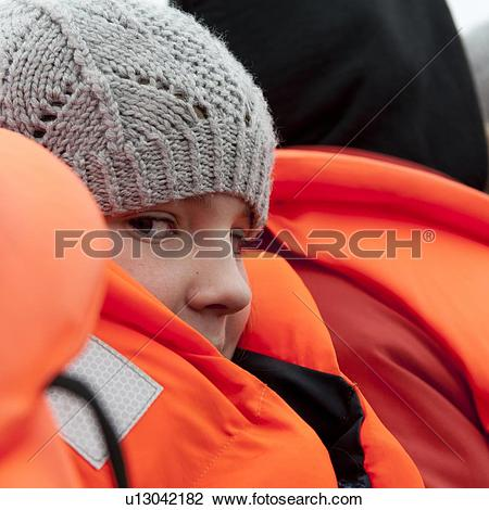 Stock Photo of Girl in fluorescent orange life preserver and knit.