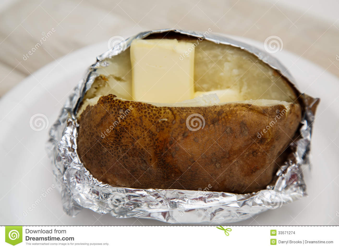 Baked Potato In Foil With Butter Stock Images.