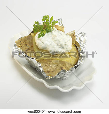Stock Photo of Baked potato with sour cream in foil, close.