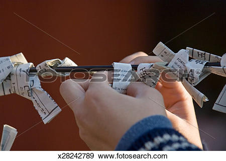Stock Photograph of Person folding paper prayers on stick, close.